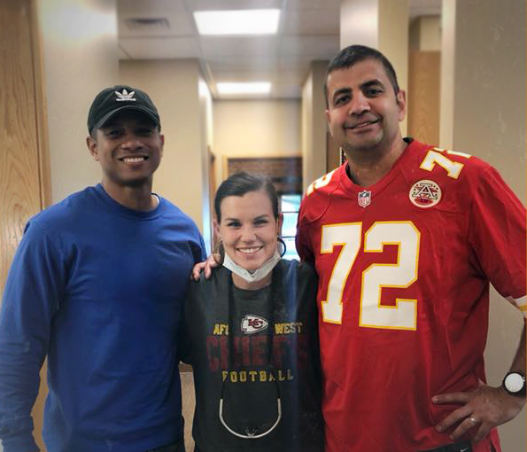 Photo of Dr. Neil Bhargava, a dental hygienist and a patient in the hall of the Wichita office. Staff are wearing KC Chiefs football shirts