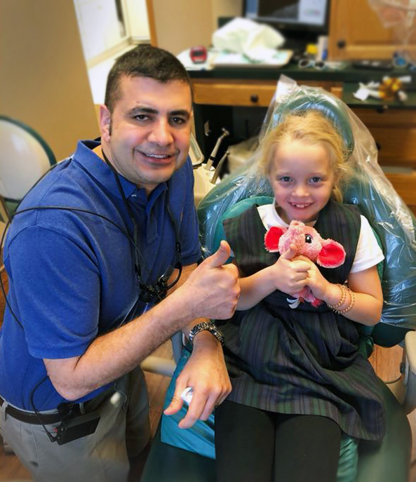 Dr. Neil Bhargava with a young girl in the dentist chair giving a thumbs up