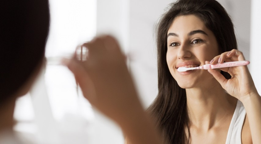 Photo of young woman looking in bathroom mirror while brushing her teeth