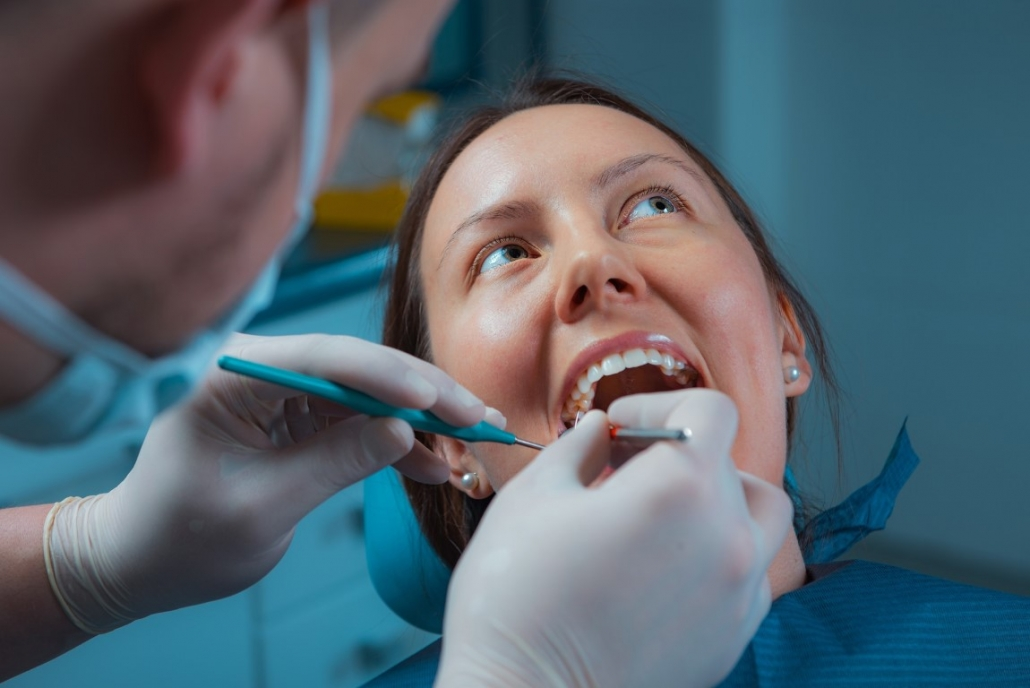 Photo of woman getting molars inspected during dentist visit by a dental hygienist